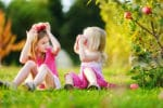 Little girls beneath an apple tree, playing with apples.
